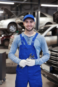 Male auto mechanic in blue overalls smiling and holding wrenches while standing among vehicles in a large garage