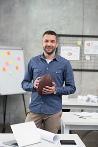 Smiling male sports agent in khakis and a button-down shirt holding a football and standing in a room with tables and charts