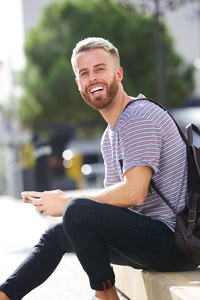 Smiling young man holding a smartphone and sitting on a concrete step outside with a backpack over one shoulder
