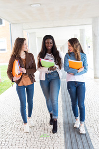 Three smiling young women holding notebooks and walking through a constructed outdoor corridor together