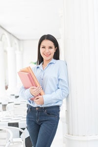Smiling young woman in jeans and a light-blue shirt holding notebooks while standing and leaning against a white pillar