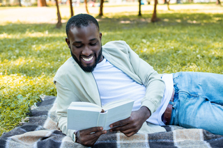Smiling young man reading a book outside in the shade while lying on a checkered blanket over grass