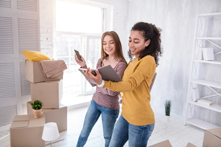 Two smiling young female college students looking at mobile devices in a bright room with moving boxes on the floor