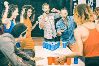 Several young men and women standing and celebrating around a white table during a game of beer pong with blue and red cups