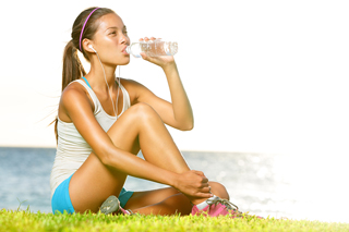 Young woman in a tank top, shorts, and running shoes drinking water from a bottle while sitting on grass by the ocean