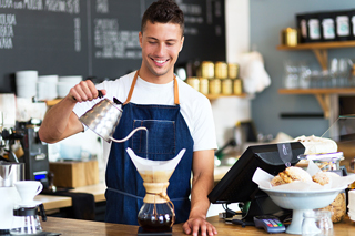 Smiling male barista at the counter of a coffee shop pouring water from a silver kettle into a filter over a coffee pot
