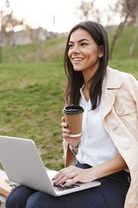 A smiling woman with one hand resting on a laptop keyboard and the other hand holding a coffee