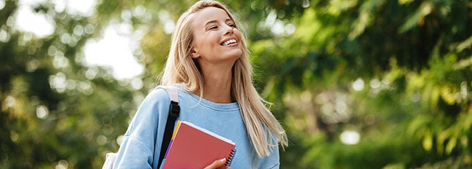 A smiling female student with a bag over one shoulder and a notebook in one arm standing near some trees