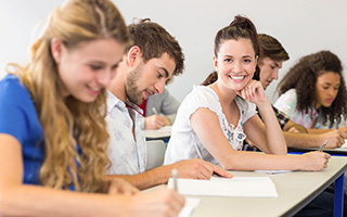 A smiling young woman sitting in a row of students working at a table