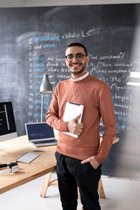 Smiling man wearing glasses, holding a digital tablet, and standing next to a desk with a computer and open laptop