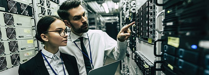 Male IT pro pointing to network hardware while standing next to a female IT pro with an open laptop in a server room