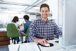 Man in a plaid shirt smiling and using a computer in a well-lit office with two people sitting at another computer behind him