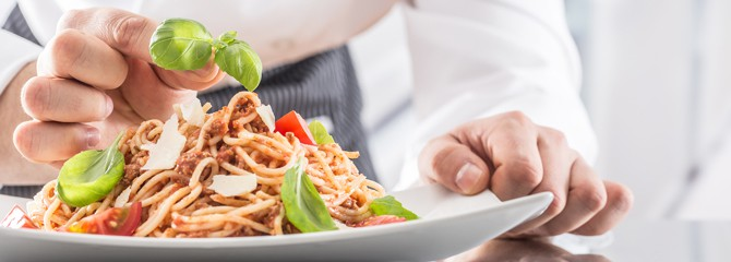 Basil leaves being placed onto a plated dish of spaghetti by the hands of a culinary professional in a white chef uniform