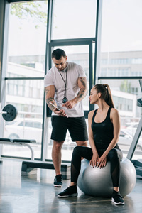 Personal trainer and client working at the gym