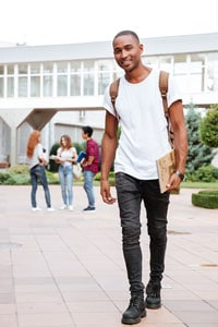 Smiling male college student in a white shirt and black pants walking outside on campus with three students in the background