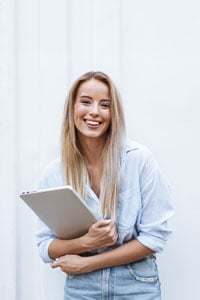 Young woman in jeans and a light-colored shirt smiling and holding a closed laptop while standing in a light-filled space