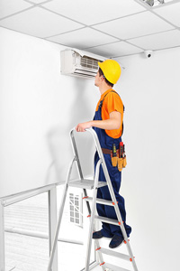Man wearing a hard hat, overalls, and toolbelt standing on a ladder to inspect a wall-mounted air conditioning unit