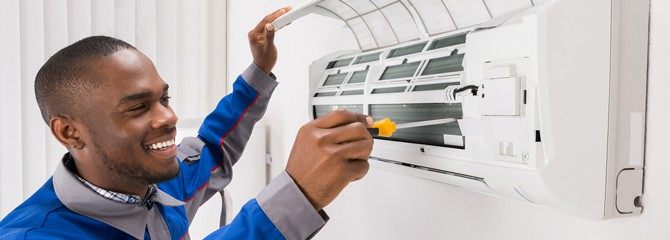 Smiling HVAC technician in a blue and gray uniform working on a wall-mounted air conditioner with a screwdriver