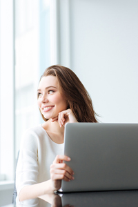 Woman smiling working on a laptop