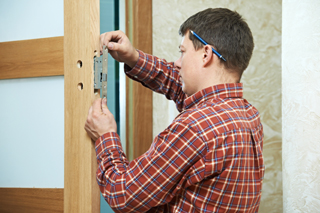 A man in a plaid shirt with a pencil behind his ear installing a lock in a wooden frame