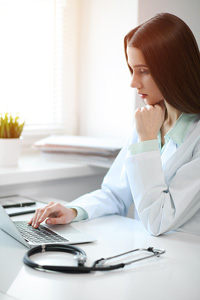 Young woman resting her chin on one hand while using an open laptop on a white desk with a stethoscope on it in a sunlit room