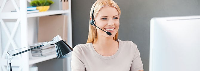 Smiling female transcriptionist wearing a headset and sitting at a computer with a desk lamp next to it in a bright office