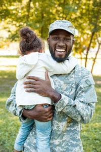 Smiling male service member in a camouflage military uniform standing outside and holding a young girl who is hugging him