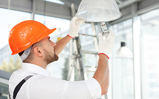 Male electrician wearing an orange hard hat and installing a bulb in an overhead lamp inside a building under construction