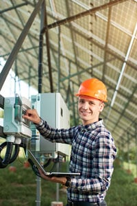 Male electrician in a plaid shirt and orange hard hat inspecting a piece of equipment beneath an array of solar panels