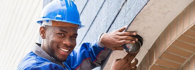 Smiling young man in a blue hard hat and work uniform inspecting a building's exterior light while standing on a ladder