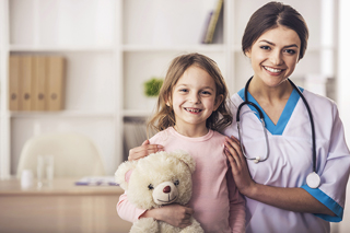 Nurse with a young patient and teddy bear