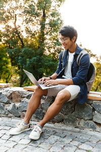 Young man in shorts sitting on a bench outside with an open laptop on his knee and a backpack strapped to his shoulders