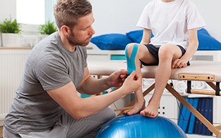 Kneeling man applying elastic therapeutic tape around the kneecap of a child who is sitting on a treatment table