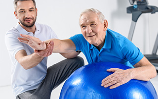 Older man leaning against a stability ball and extending one arm while another man kneels beside him and guides the arm