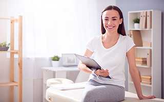 Smiling woman sitting on a massage table and holding a clipboard