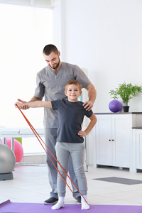 Man helping a child who is stepping on a resistance band and extending it with one arm straight out to the side
