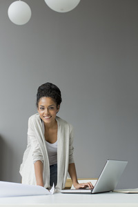A smiling young woman with one hand leaning on a sheet of paper and the other hand resting on a laptop keyboard