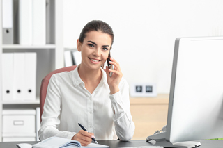 A smiling woman sitting at an office desk writing in a notebook and holding a phone to her ear