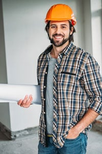 Smiling man in a plaid shirt and orange hard hat holding blueprints and standing inside a building under construction