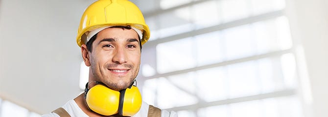 Man wearing work overalls, yellow hard hat, and safety earmuffs around his neck while standing inside a light-filled building