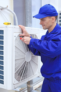 Man in a blue hat and technician uniform using a screwdriver to work on air conditioning equipment outside a building
