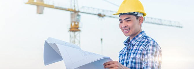 Smiling young man in a plaid shirt and yellow hard hat looking at paper blueprints in front of a construction crane outside
