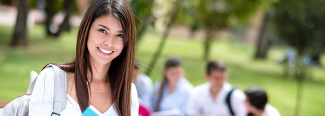 Smiling young woman standing outside with a gray backpack in front of a small group of sitting college students